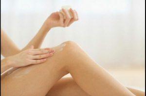 Femme qui s'applique de la crème hydratante sur les jambes